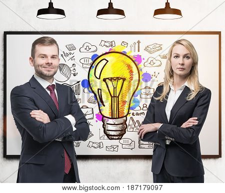 Bearded young businessman and his blond beautiful colleague are standing with crossed arms near a whiteboard with a business idea sketch. Toned image