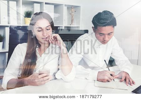 Young Asian businessman is writing in his notebook. His beautiful colleague is looking at her smartphone screen.  Toned image double exposure
