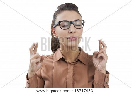 Isolated portrait of a young businesswoman with long hair wearing a brown blouse and glasses and standing with her fingers crossed with closed eyes.