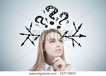 Portrait of a dreamy blond businesswoman standing near a gray wall with question marks and arrows pointing to different directions
