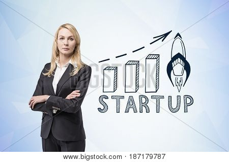 Portrait of a confident blond businesswoman standing with crossed arms near a blue wall with a start up graph drawn on it