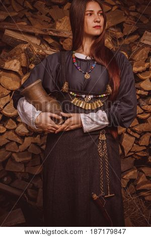 Scandinavian middle class woman in historical suit posing with jar over firewoods. Her apparel based on archaeological sites on Gotland island. Late 10th - 11th centuries.