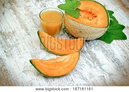 Tasty and juicy melon - cantaloupe and melon juice (smoothie) on rustic table