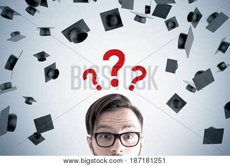 CLose up of a young man s head. He is wearing glasses and standing near a gray wall with graduation hats and three question marks above his head