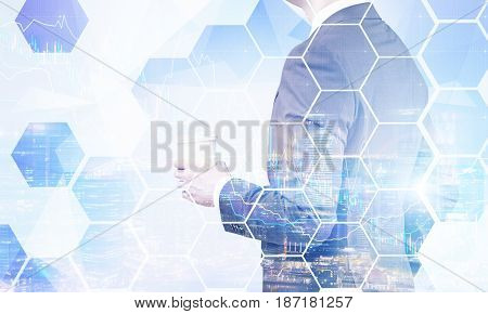 Side view of an unrecognisable businessman holding a paper cup of coffee and standing against a night city panorama with graphs. Mock up toned image double exposure