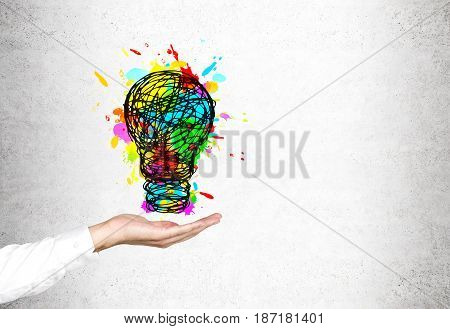 Close up of a businessman s hand in a white shirt holding a large colorful light bulb sketch drawn on a concrete wall. Mock up