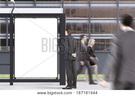 Business people are passing by a bus stop with a blank vertical poster standing in a street near an office building. 3d rendering mock up