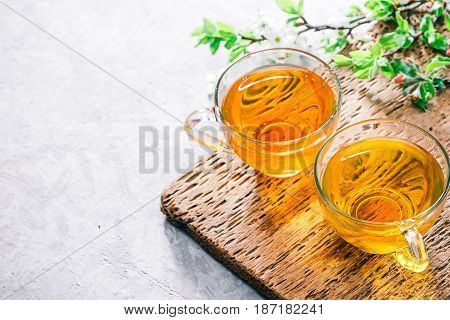 Herbal tea in glass cup. Concrete background with wooden trivet and plum tree flowers. Selective focus