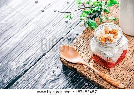 Ricotta with jelly and almonds in glass jar. Textured black wood background with apple blooming twigs. Selective focus