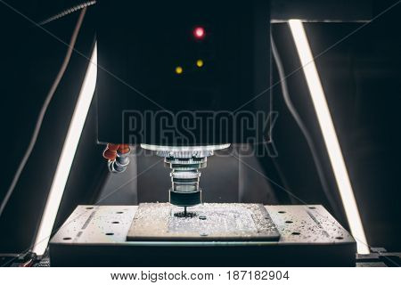 Front view of CNC milling process: high speed rotating cutting tool and moving table with fixed unmanufactured aluminum piece on it during metal treatment with two LED lamps in the background