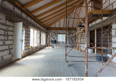 Interior of apartment with ladders during under renovation remodeling and construction (preparing to plaster)