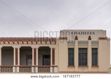 Napier New Zealand - March 9 2017: Part of Art Deco Facade of hotel in Emerson shopping street against silver sky. The word Chambers is painted big on the wall. Windows and corridor.