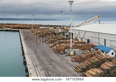Napier New Zealand - March 9 2017: Overview of part of large timber harbor under cloudy sky. Heaps of brown tree trunks sawed at fixed length. Pacific Ocean in back. Building and light poles.
