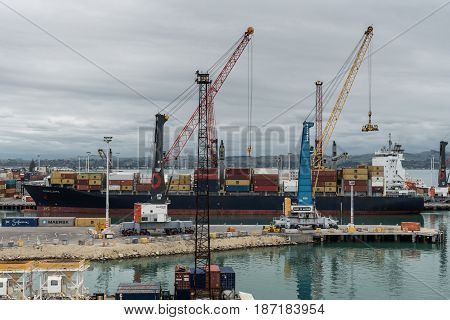 Napier New Zealand - March 9 2017: Penelope container ship unloads in the commercial port under heavy skies. Piles of containers cranes and other harbor installations.