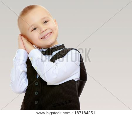 Beautiful little blond boy in a fashionable black suit with a tie.He keeps his hands near your ear.On a gray background.
