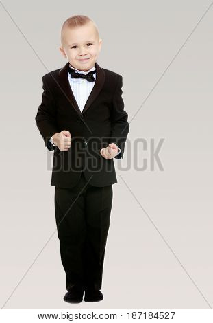 Beautiful little blond boy in a fashionable black suit with a tie.The boy tightly clenched his fists.On a gray background.