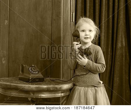 The little girl in the interior of the fifties of the last century keeps the ear-hook of vintage phone. The girl calls her grandmother.Black-and-white photo. Retro style.