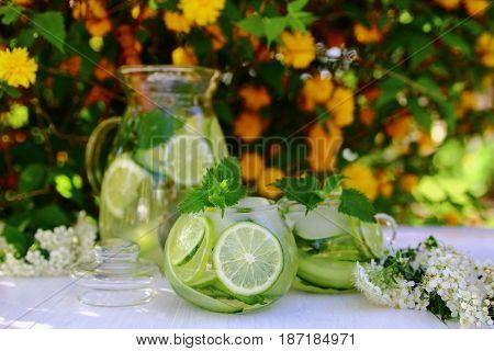 lemonade with cucumber and lime with white flowers on the table in the garden