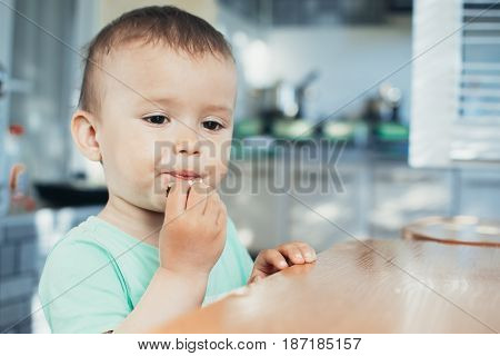 The Child In The Kitchen Eating Bread