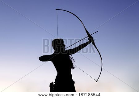 Female ginger hair archer shooting targets with her bow and arrow. Concentration, target, success concept. Copy space text.