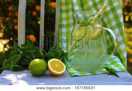 lemonade in a glass pitcher on an old chair in the garden