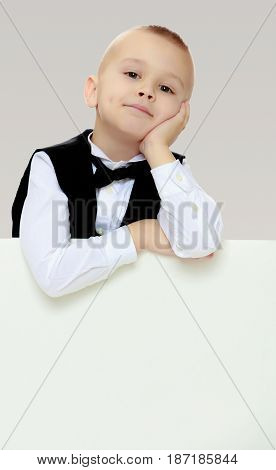 Cute little blonde boy in a black waistcoat and a white shirt and a bow at the neck , peeping over white banner.He put his head on his hand.On a gray background.