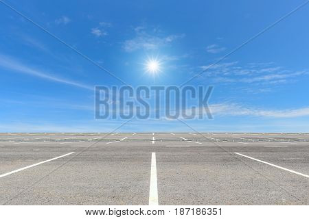 Empty parking lot on blue sky and sun reflection
