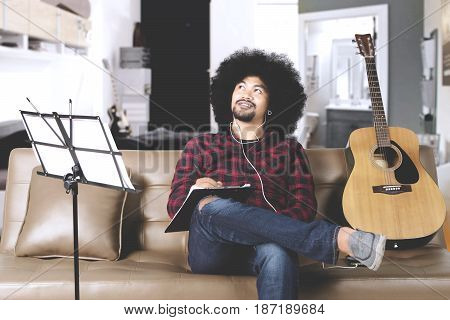 Young afro man composing a song while listening music on earphone at home