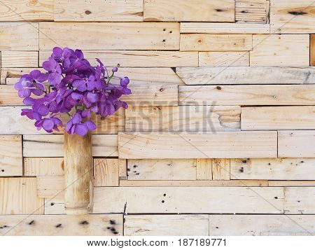 Violet vanda orchid in bamboo vase hanging on wooden plank wall. Shabby vintage interior style.