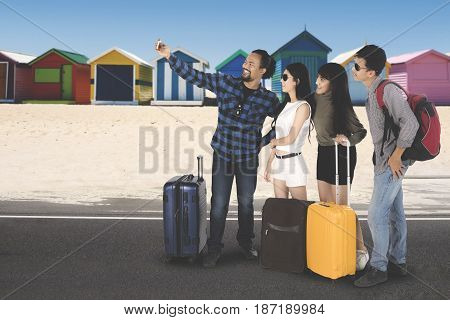 Picture of an Afro man using a smartphone for taking a picture together with his friends in the beach cottage