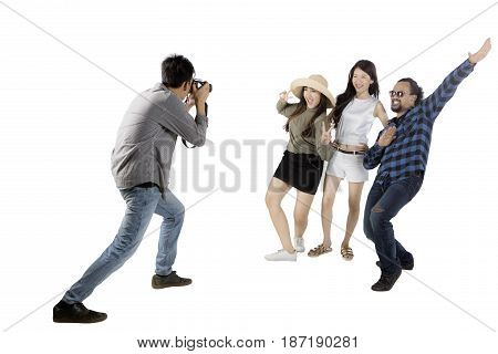 Asian man using a digital camera for taking a picture his friends while standing in the studio