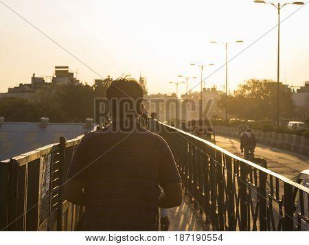 people walk on sidewalk in sunlight in Delhi city India.