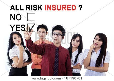 Asian businessman using a pen while selecting a yes option with text of all risk insured in the meeting