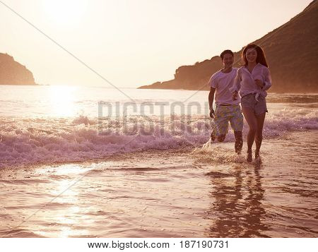 happy young asian couple running on beach in during sunset or sunrise.