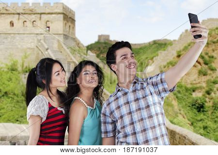 Multiethnic teenagers taking self portrait together in the Great Wall of China