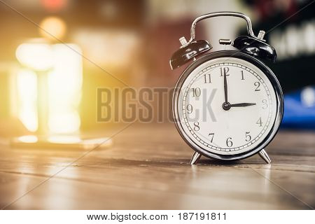 3 O'clock Time Retro Clock On Wood Table With Sun Light Background