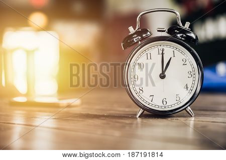 1 O'clock Time Retro Clock On Wood Table With Sun Light Background