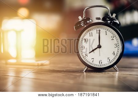 8 O'clock Time Retro Clock On Wood Table With Sun Light Background