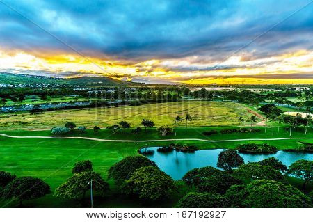Sunrise over the horizon with sun peeking under dark morning clouds at the resort community of Ko Olina on the island of Oahu in the island state of Hawaii