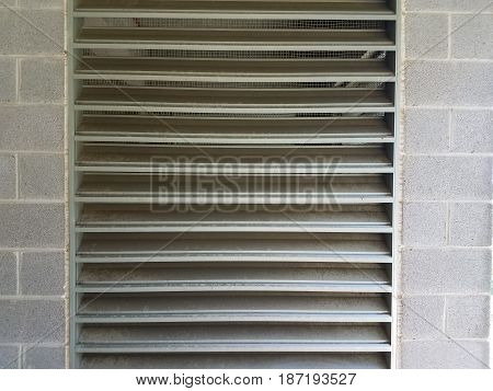large grey vent with grey cinder block wall
