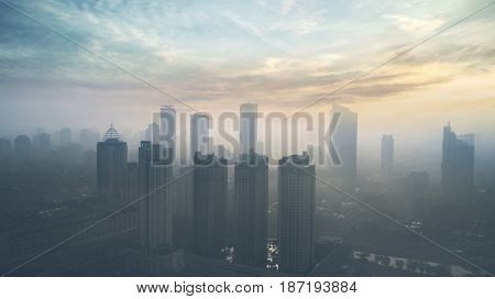 Beautiful aerial view of Jakarta city with skyscrapers on the misty morning at sunrise time