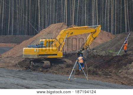 Reconstruction of the road in countryside - yellow excavator at work, telephoto