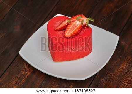 Red strawberry cake in the shape of heart on Valentine's Day on wooden background