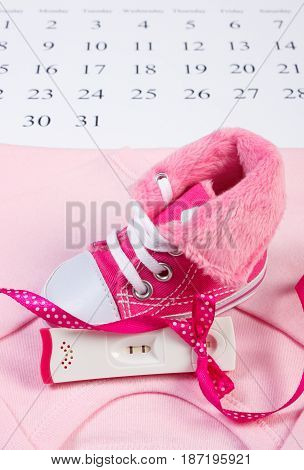 Pregnancy Test With Positive Result And Clothing For Newborn Lying On Calendar, Expecting For Baby