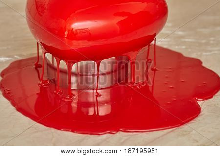 Process of pouring red glaze on heart shape form mousse cake homemade food