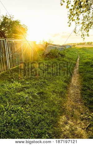 Countryside at sunset. Rural path and fence