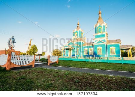 Krasnyy Partizan, Dobrush District, Gomel Region, Belarus. Old wooden church of the birth of the Virgin Mary of Orthodox Christians next to the memory of the dead soldiers during the Second World War