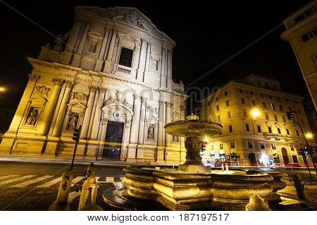 Sant Andrea della Valle is a basilica church in Rome, Italy, in the rione of Sant Eustachio. Night. Lampposts, signs and bright car headlights.