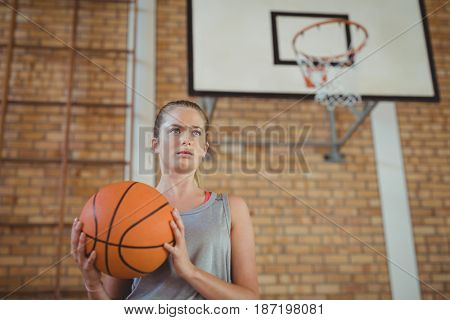 Determined girl holding a basket ball in the court