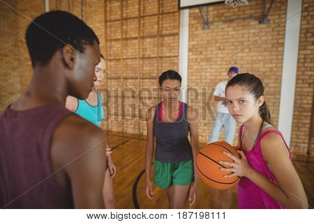 Concentrated high school kids playing basketball in the court